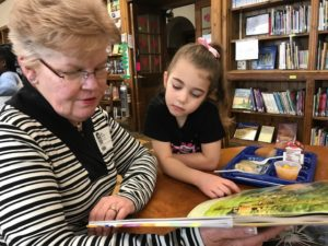 A woman from the community reads with an elementary student in the library during lunch