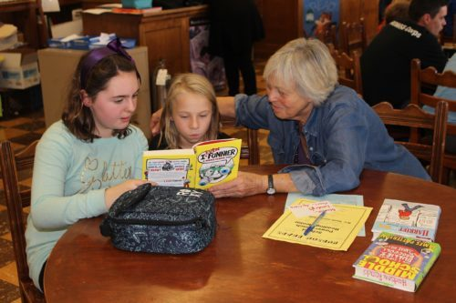 A woman from the community reads with elementary students in the library during lunch