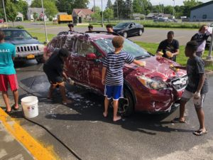junior high boys washing cars