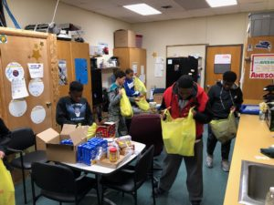 junior high boys packing bags for the food drive
