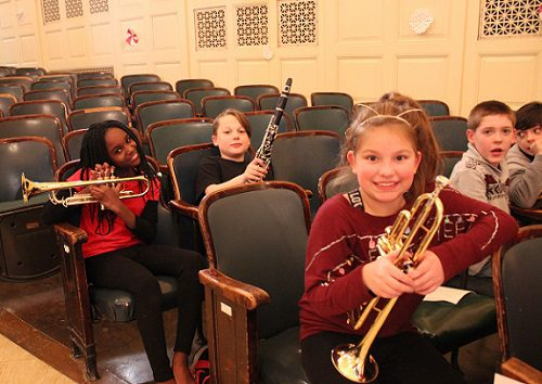 elementary students holding band instruments