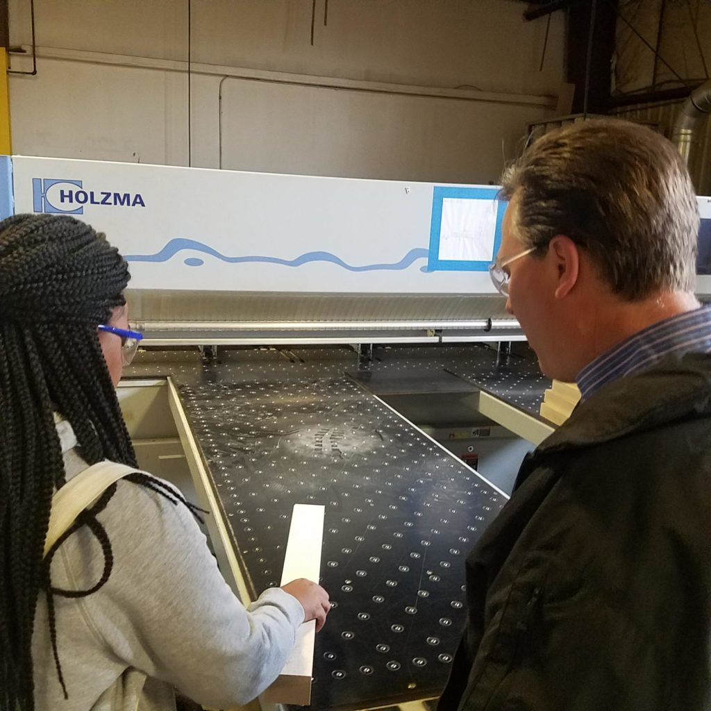 teacher and student look at manufacturing equipment