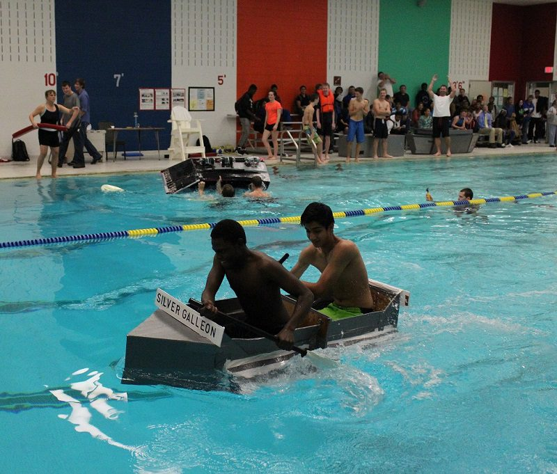 Students paddle a cardboard boat across the pool