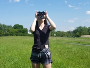 student looking at sky with binoculars