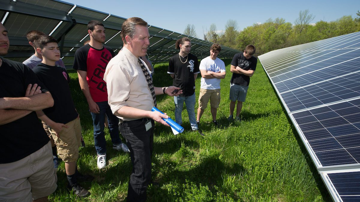 teacher and students discuss energy by solar panels