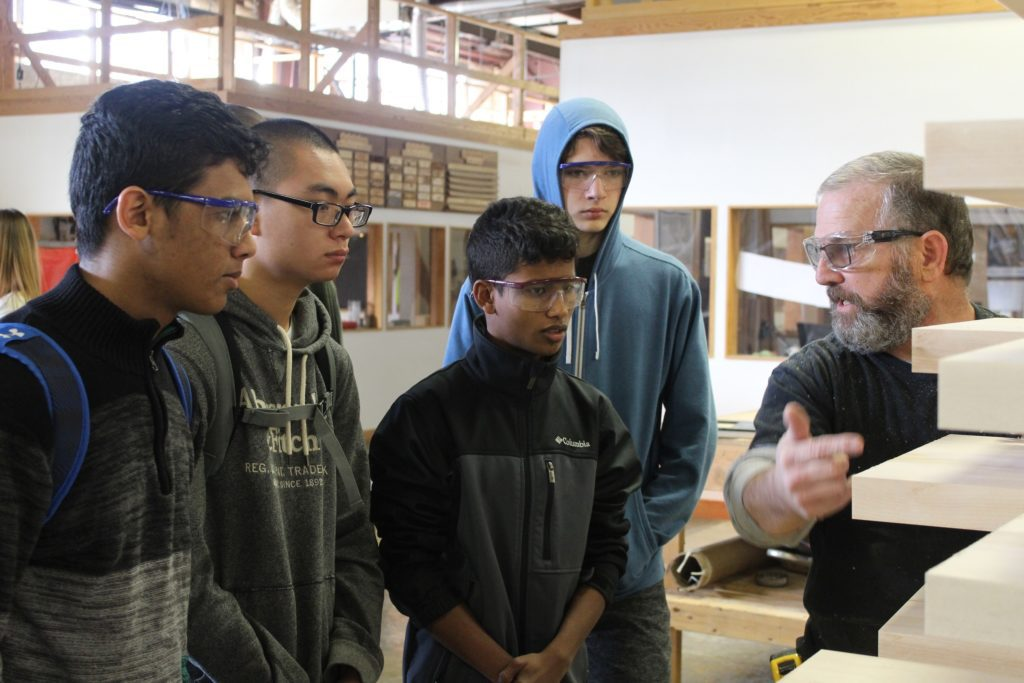 a shop employee shows students the pieces of wood he is manufacturing
