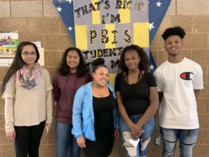 students stand in front of a P.B.I.S. banner