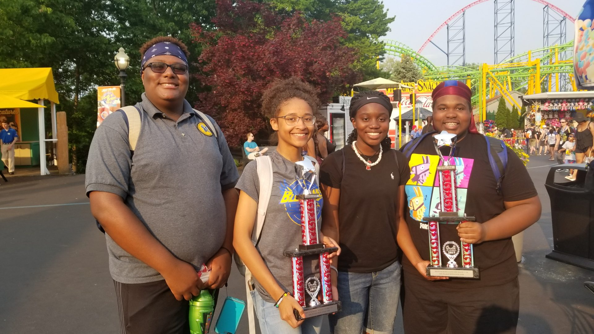 students at amusement park hold trophies