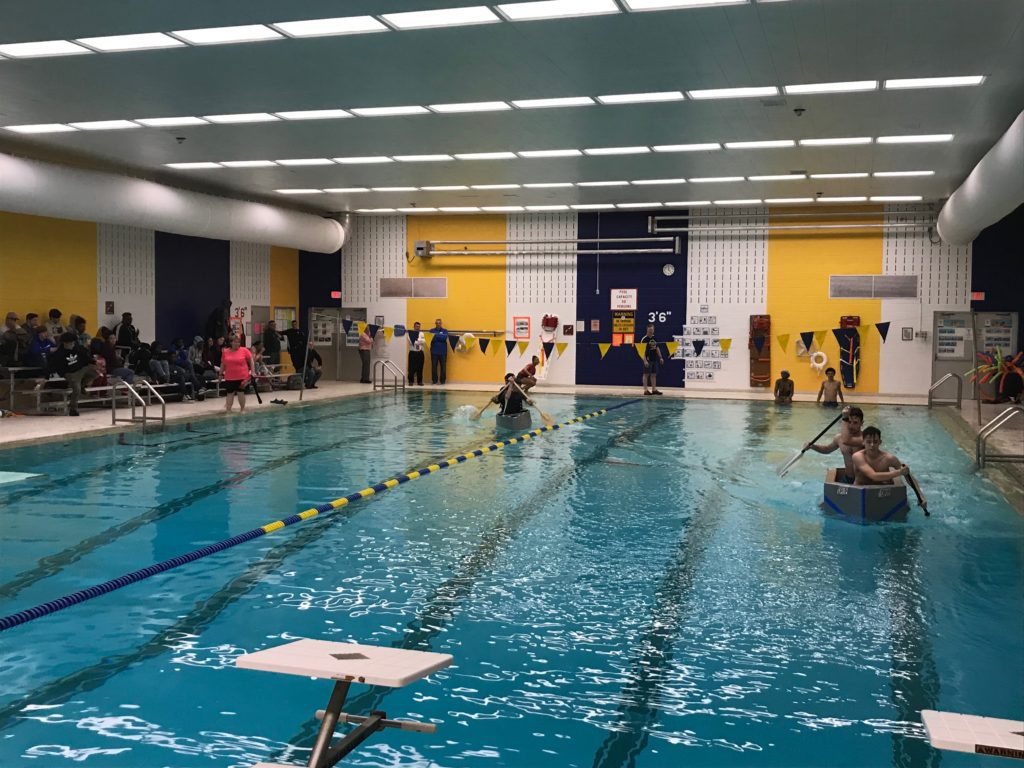 students paddle in cardboard boats across indoor swimming pool