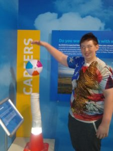 student works with interactive exhibit at science museum