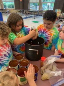 elementary students add sauce ingredients to a large pot