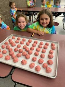 young girls smile with a tray of meatballs