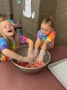 young girls mixing meatballs in a bowl