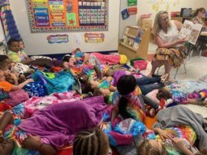 Ms. Ruud reads a book to children on the floor
