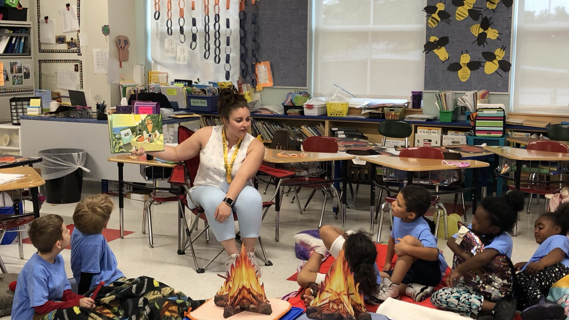 a guest reader reading to children in a camp-themed classroom
