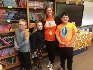 teacher and students wearing orange