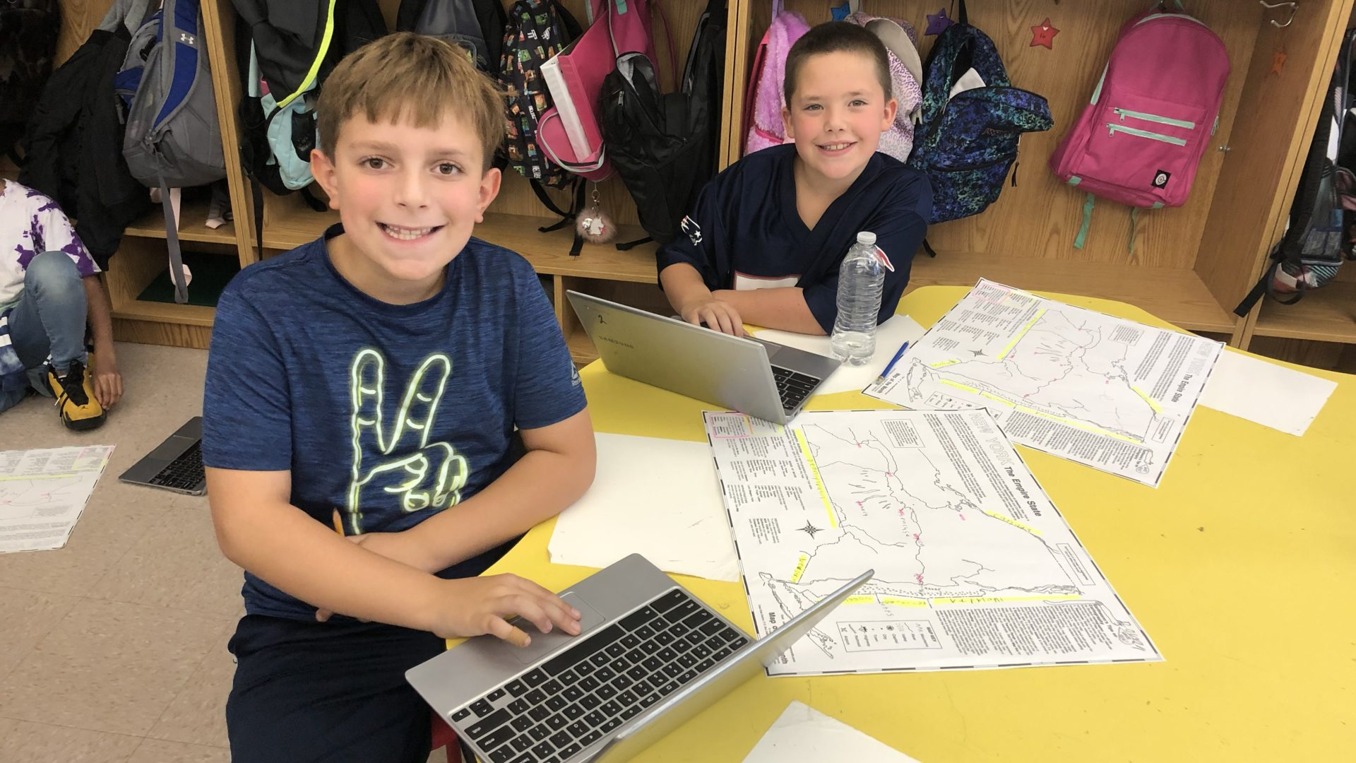 elementary boys studying maps of New York State