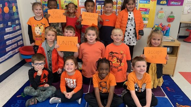 elementary children wearing orange shirts