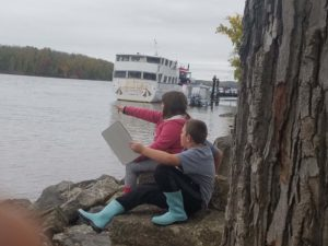 two children sketching by river