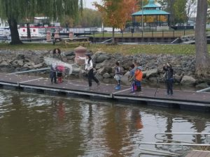 children and teacher throwing a net in the river