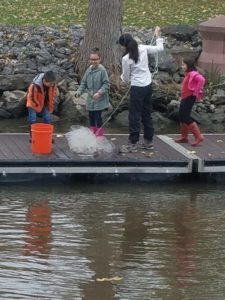 children and teacher standing dock