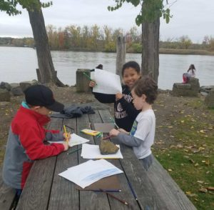 children drawing at a picnic table
