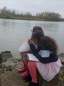 two girls sketching by river