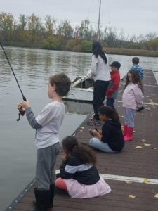 children and teacher fishing off dock