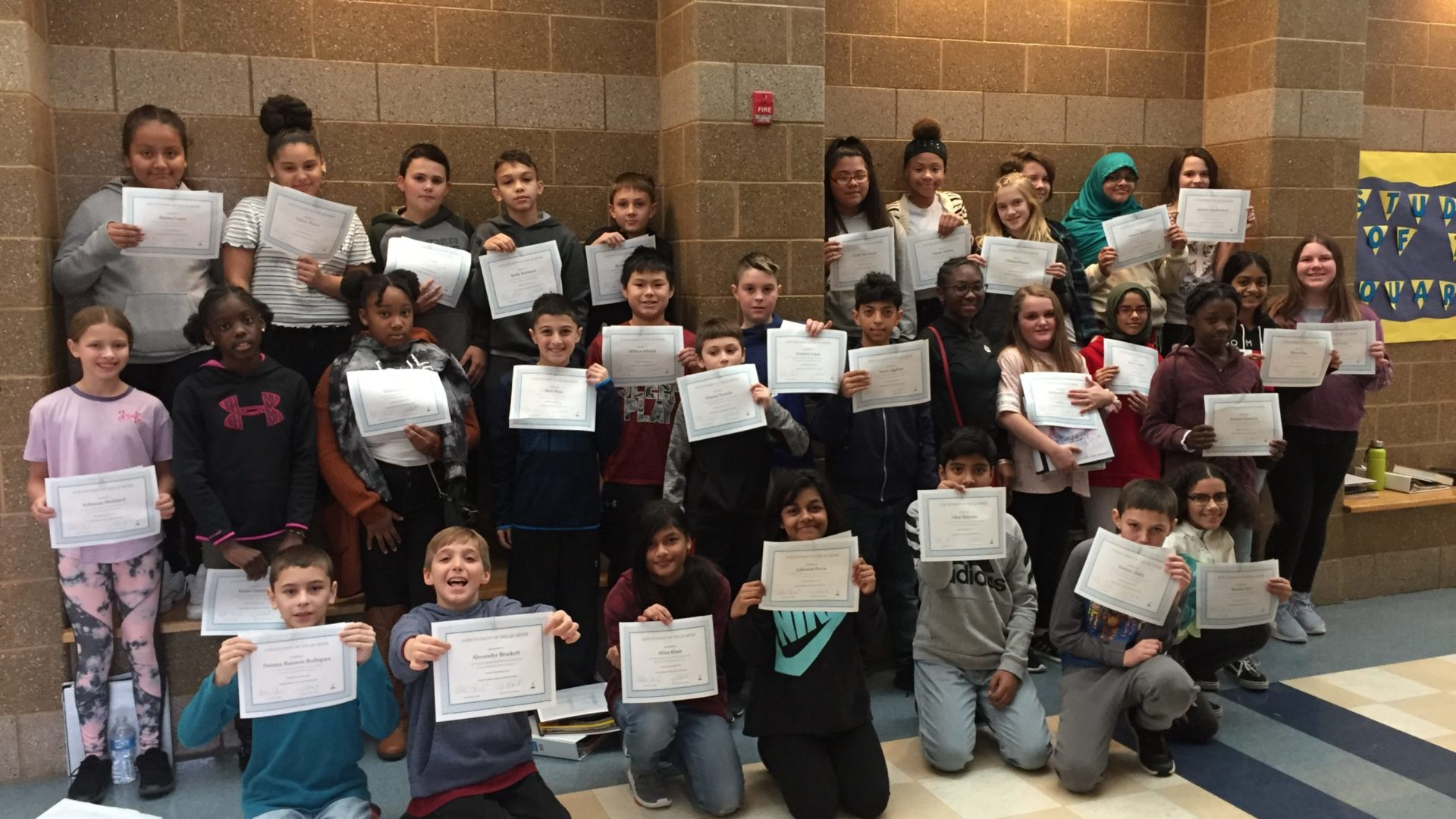 students stand holding certificates