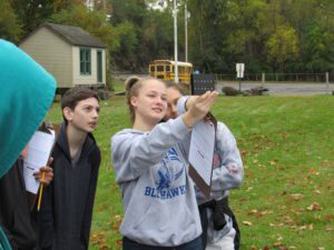 students hold up scientific device to evaluate water samples