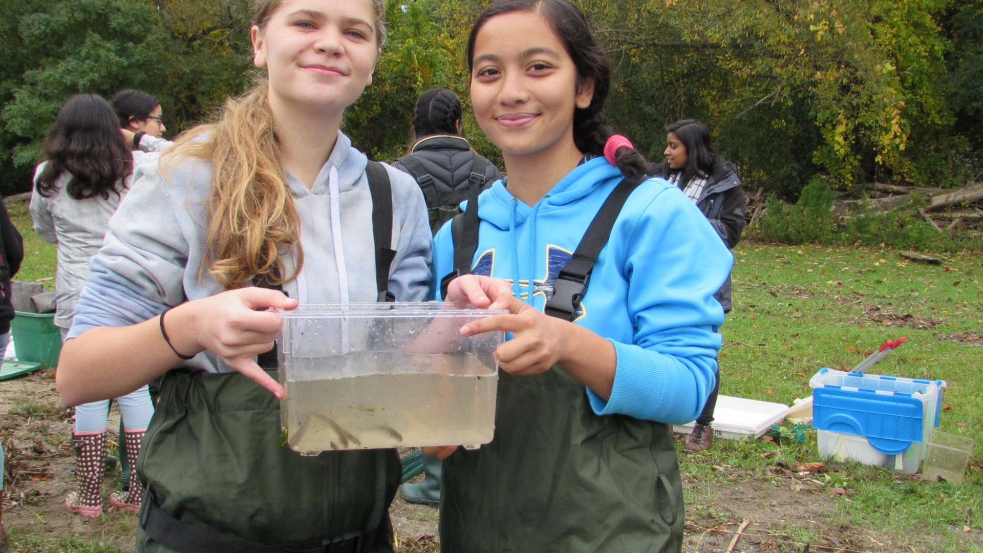 two girls in water waders holding a container with river water