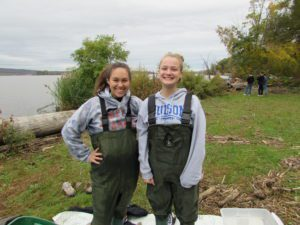 two girls wearing chest waders by river