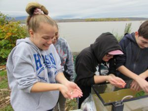 students hold small fishes in hands