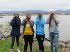 four girls holding binoculars by river