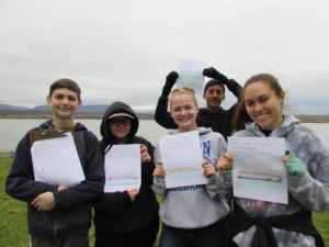 five students holding papers by the river
