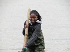 student wading in river and holding seine net