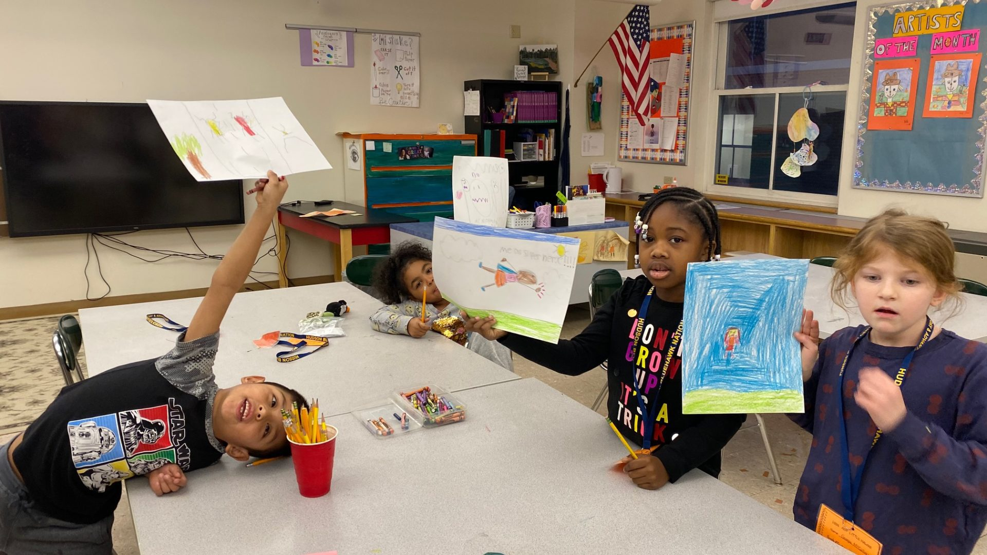 children hold up super hero drawings