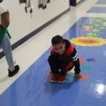A student demonstrates how to use the sensory path in the first grade hallway.