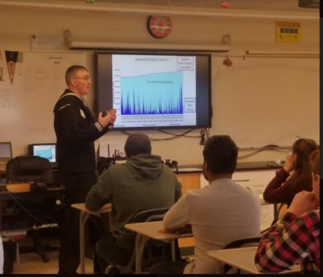Navy representative showing graph to students
