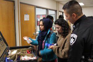Deputy and students examining a medical kit