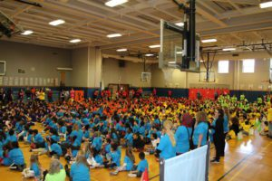 gymnasium filled with students and teachers in colorful t-shrits