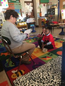 a woman reads to elementary students seated on floor