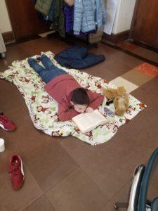 a boy reads on a blanket