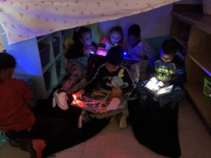 elementary students read together in a blanket fort
