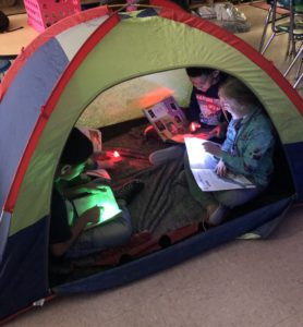 elementary students read together in a tent in the classroom