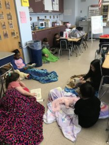 elementary students read under blankets
