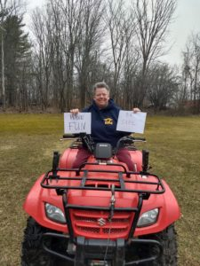 teacher holding paper with handwritten message on ATV