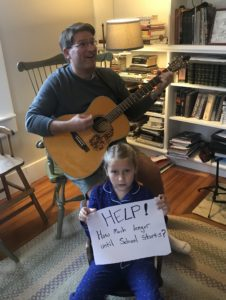 kid holding paper with handwritten message while dad plays guitar