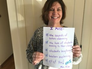 teacher holding paper with handwritten message