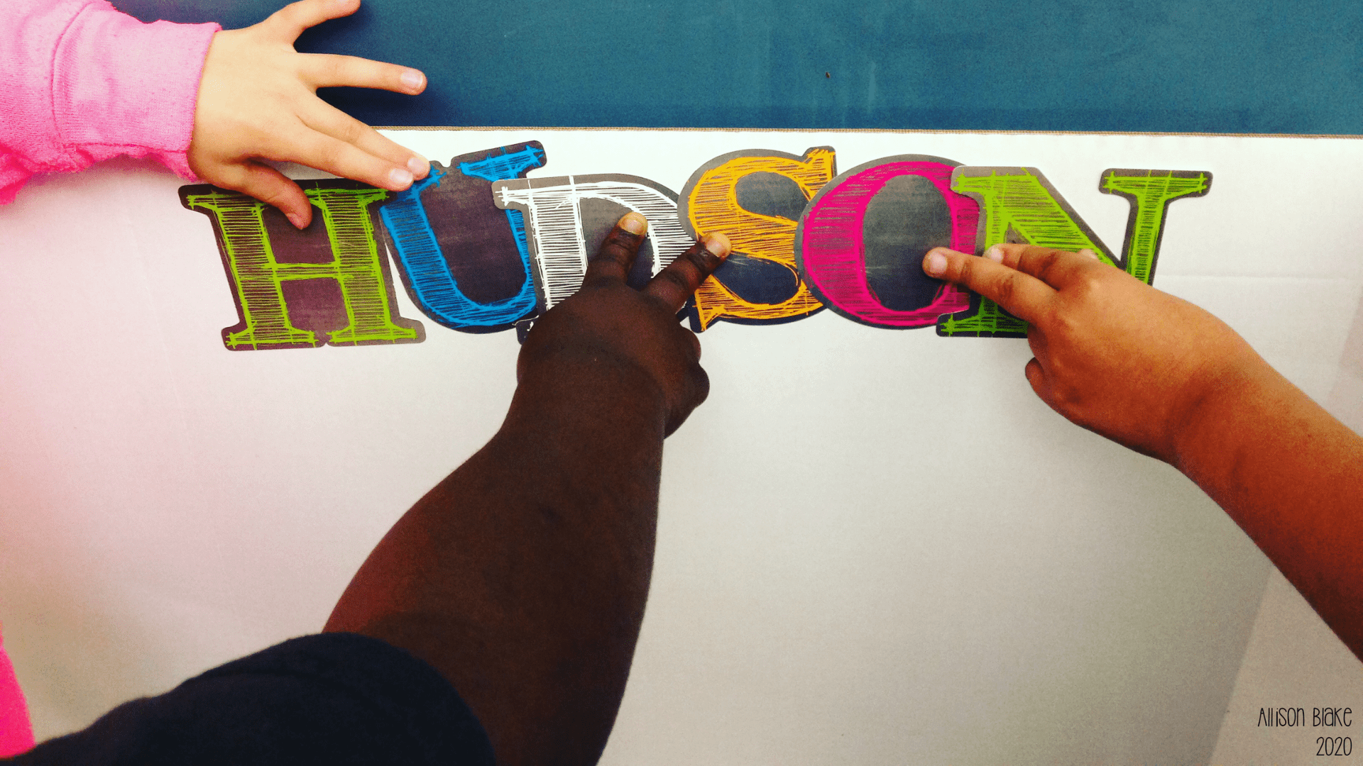 "three children's hands touching ""Hudson"" sticker"